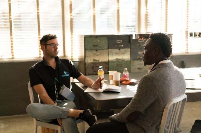 Zwei Männer sprechen sitzend über das Eck eines Tischs für ein Kundeninterview