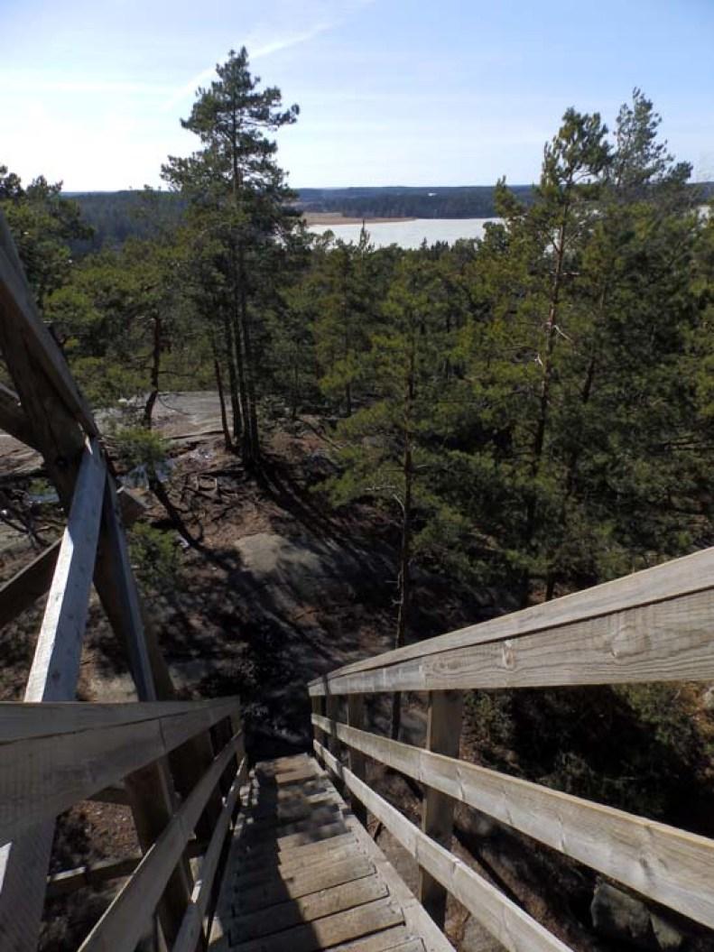 Laskeutuminen Vaarniemenkallion näkötornista männikköisille kallioille. Tornista avautuu näkymä Pitkäsalmelle.