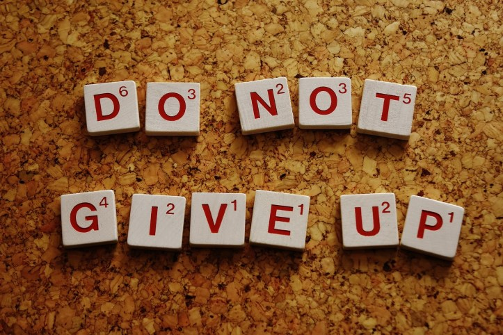 "Motivational message in scrabble letters, reading, ""do not give up"""