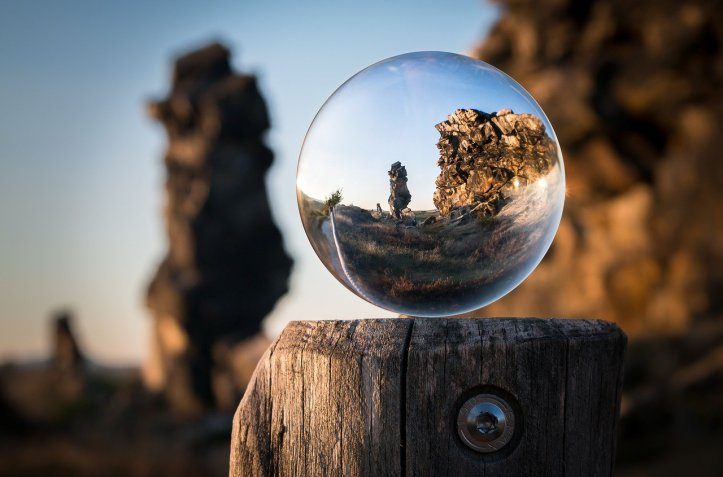 glass sphere sitting on a tree stump focusing on the background