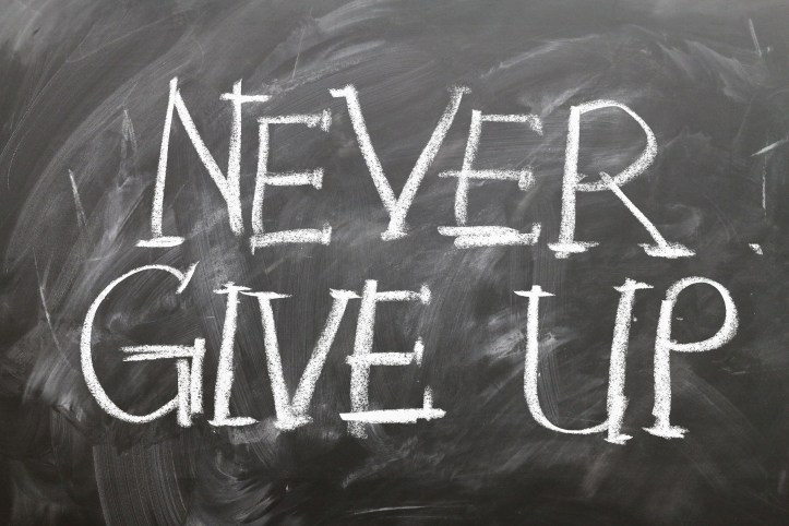 "chalkboard with with writing that says ""never give up"""