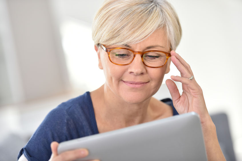 48552449 - senior woman with eyeglasses browsing on digital tablet