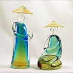 Set of two Italian Sommerso art glass Oriental figures in blue & yellow under clear glass with gold flecks in hats.