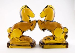 Rearing horse bookends made of solid amber glass in the 1940s. L.E. Smith and Fostoria made this form with only slight differences in the mold.