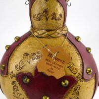 """The original leather tag hanging on the neck of the decanter reads """" Noymez, Real Leather, Hand Made in Italy""""."""