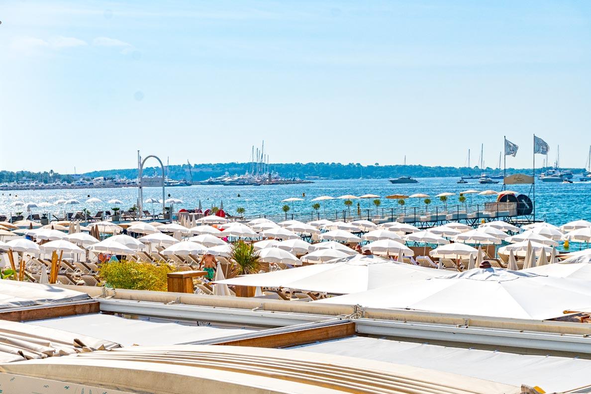 Der Strand von Cannes: weiße Sonnenschirme im Sand
