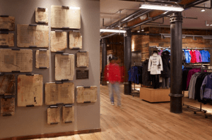 The new store melds REI's rugged outdoor aesthetic with the storied building, featuring unique aspects, such as 30 stone printing tables from the early 1900s.