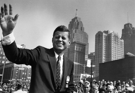 John F. Kennedy waves to a crowd in front of Cobo Hall, in Detroit
