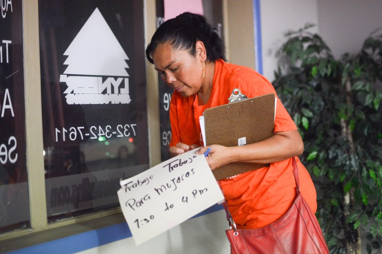 "Reynalda Cruz removes a New Jersey temp agency window sign that reads, ""Trabajo Para Mujeres,"" or ""Work for Women."" Cruz was a temp worker for many years before joining New Labor, a workers advocacy group."