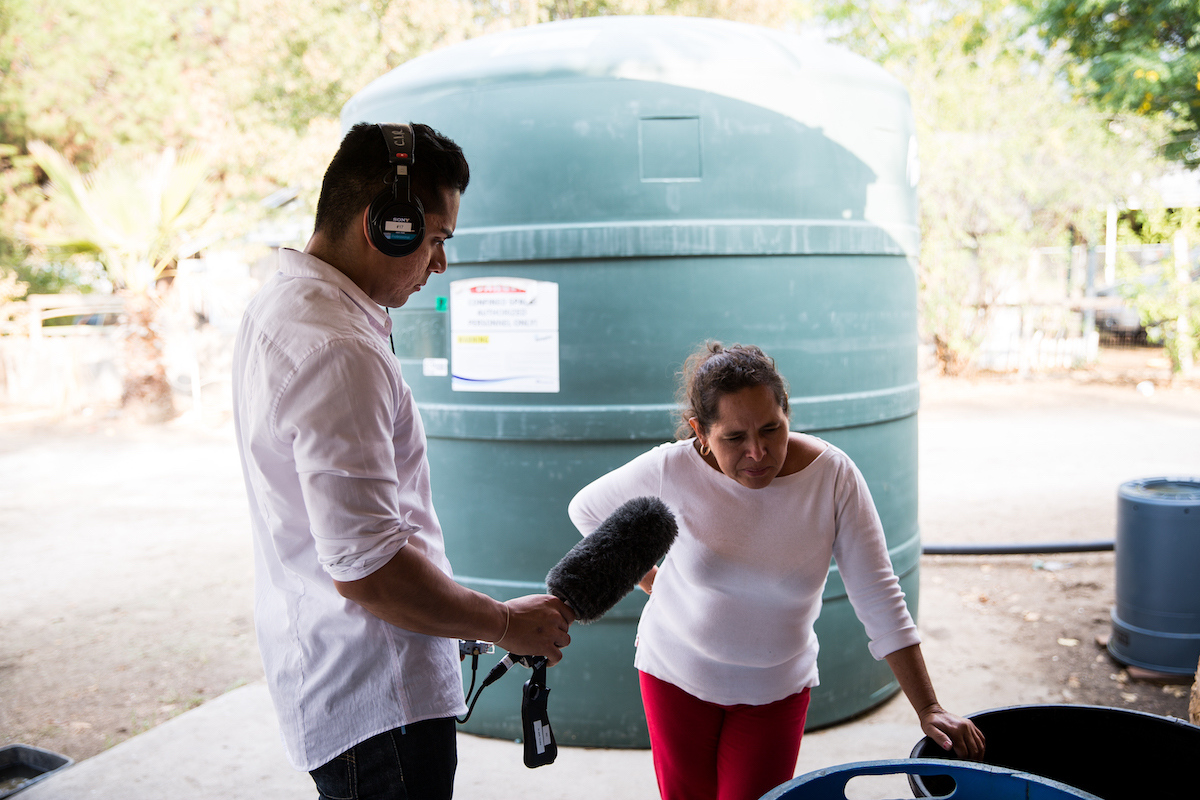 A reporter with a microphone interviews a woman in front of a water tank