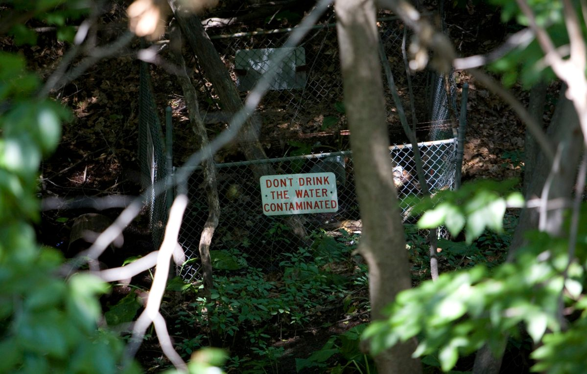 """A sign next to a creek in the woods warns """"Don't drink the water"""""""