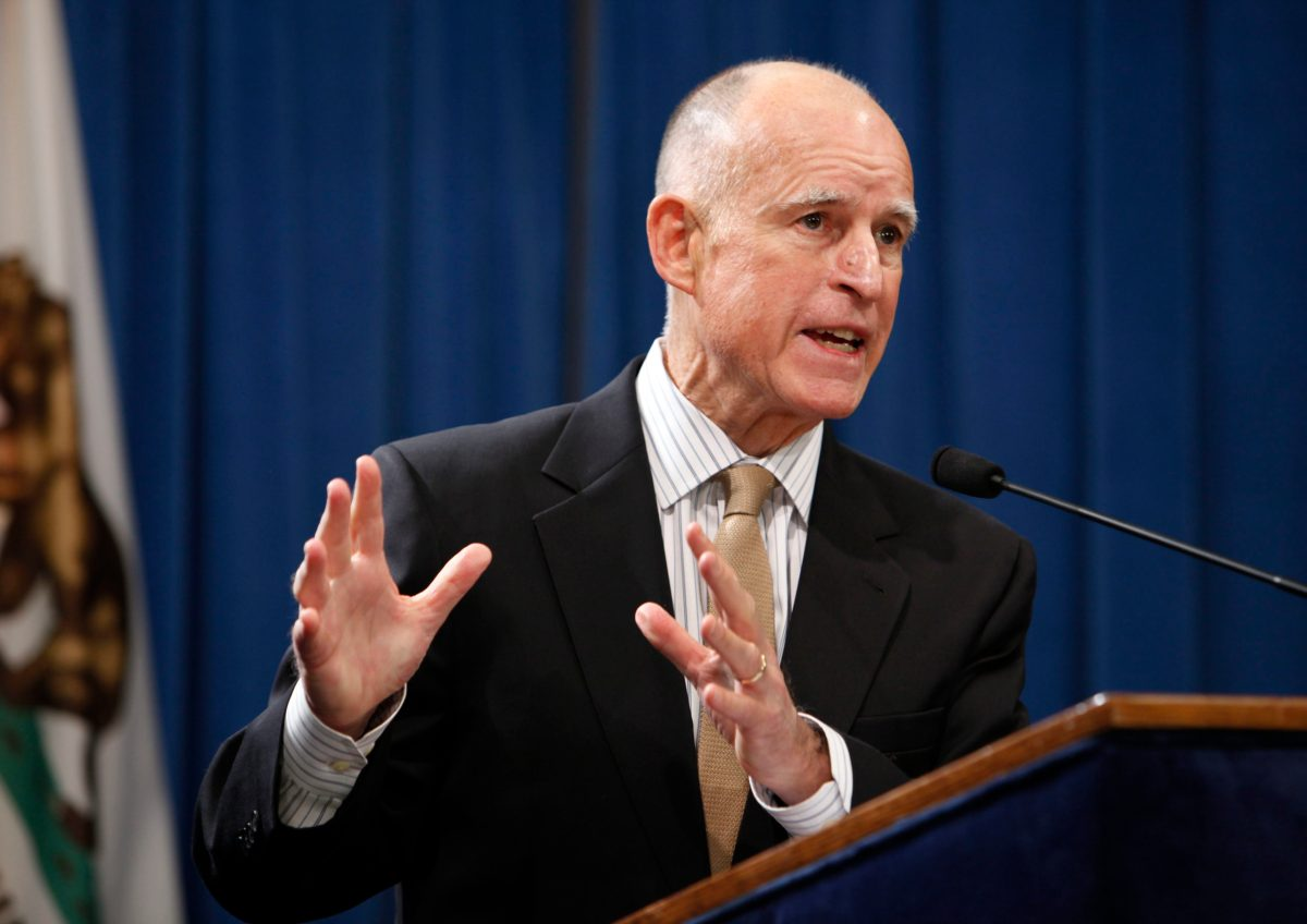 Governor Jerry Brown looking concerned and speaking at a podium.