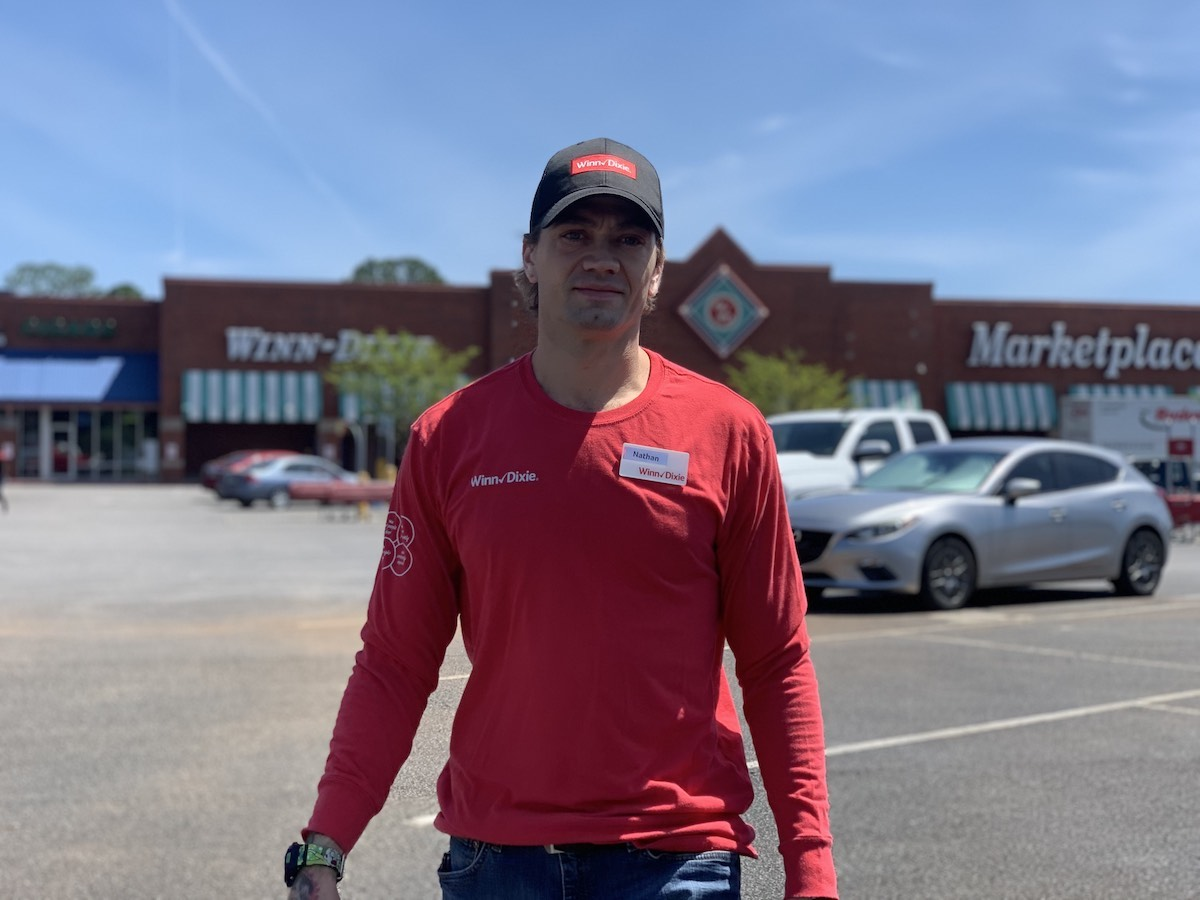 Nathan Tetreault, wearing a red uniform t-shirt and baseball cap, walks in the parking lot of a Winn-Dixie grocery store