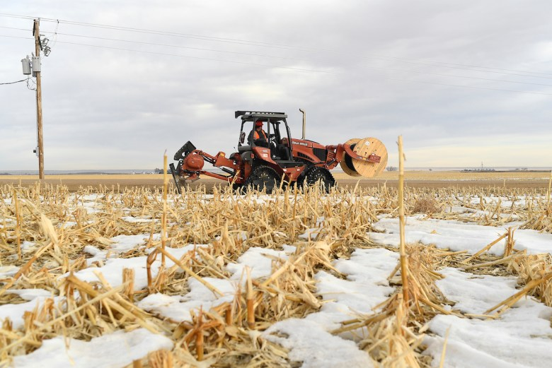An industrial digging machine lays cable through a corn field in the middle of winter.