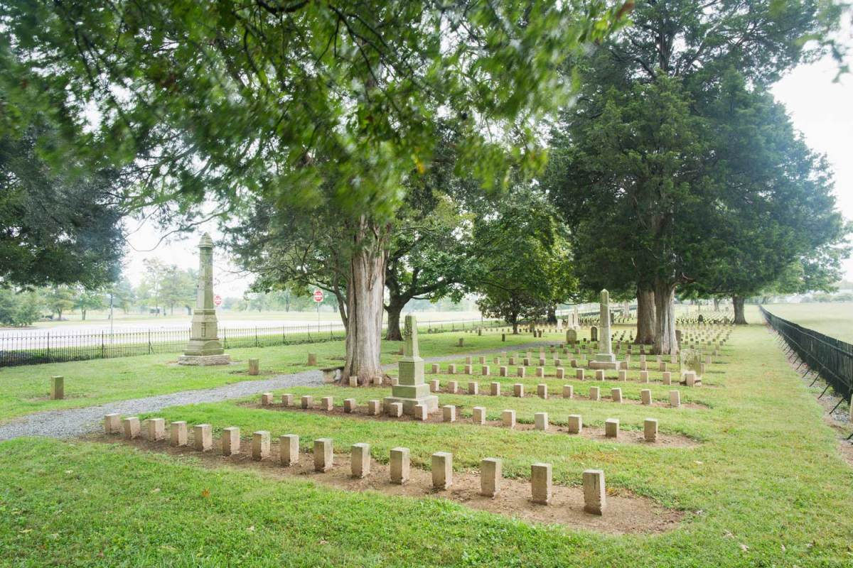Headstones form neat rows in a fenced, well-manicured cemetery.