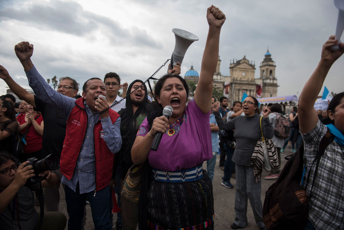 Protesters yell and raise their fists in the air. One holds a microphone; another holds a megaphone.
