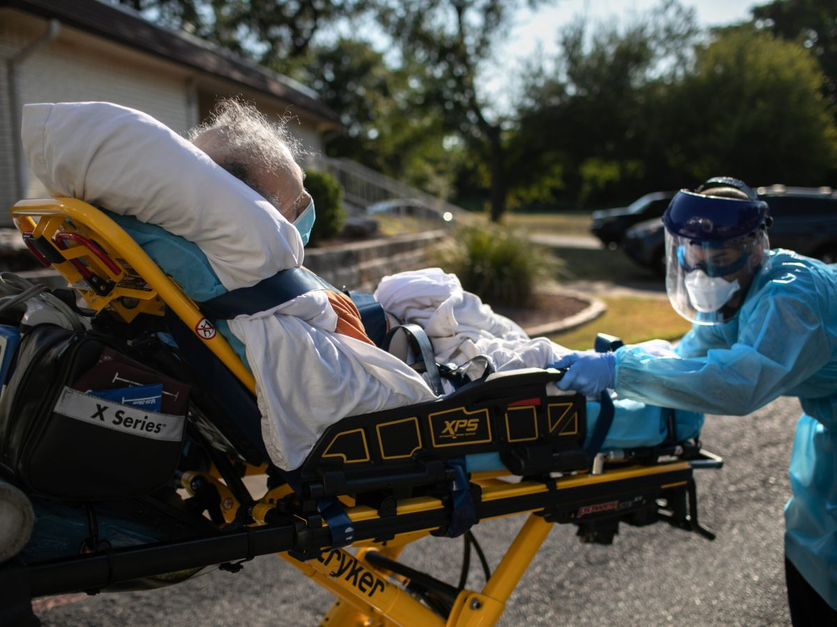 A man wearing a face mask is strapped to a gurney pushed by a paramedic. The paramedic wears a full complement of personal protective equipment.
