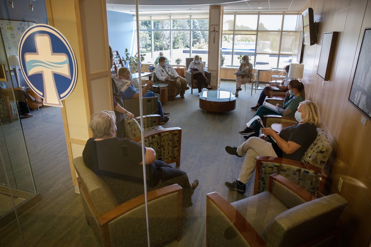 Ten medical workers sit in chairs spaced several feet apart in a hospital waiting room. Each person wears a face mask.