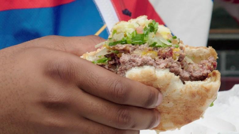 A close-up shot of a person holding a partially eaten hamburger.