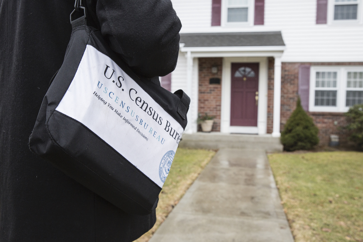 A person carrying a bag with a Census Bureau logo approaches the front door of a house.