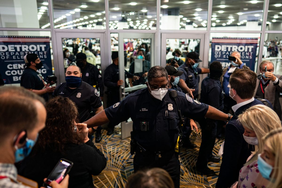 Police officers wearing masks stand outside of a convention center room with their arms wide open. A crowd of people surrounds them.