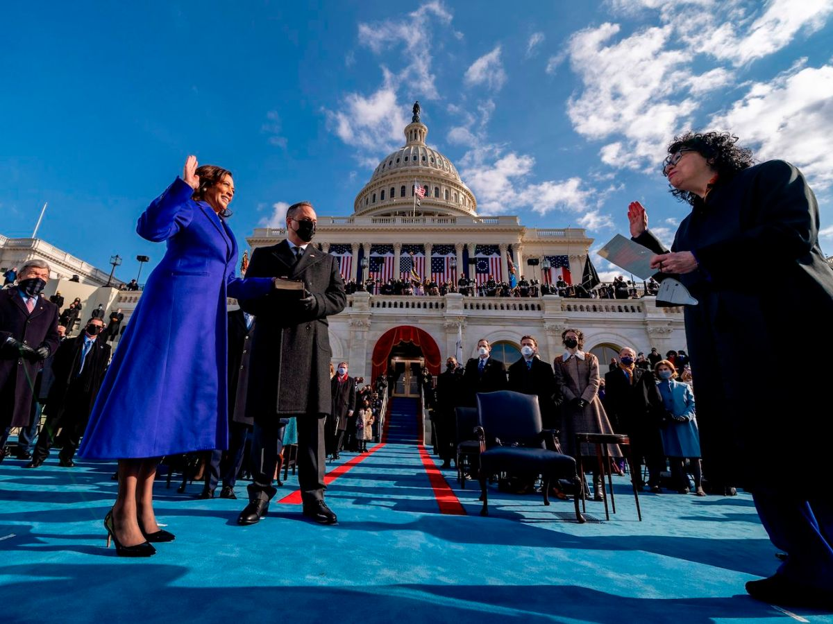 Kamala Harris, in a long blue coat, smiles as she holds up her hand to be sworn in as Vice President. Behind her is the US Capitol, decorated with American flags. Justice Sonia Sotomayor stands several feet away, dressed in her judges robe and swearing Harris in.
