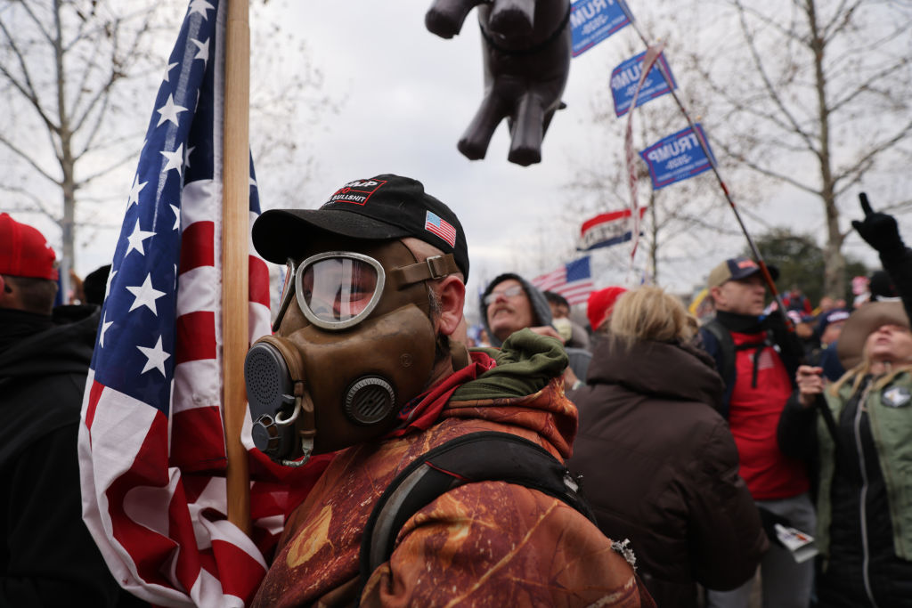 A trump supporter wearing a gas mask and waving an american flag stands in an unruly crowd outside the Capitol building.