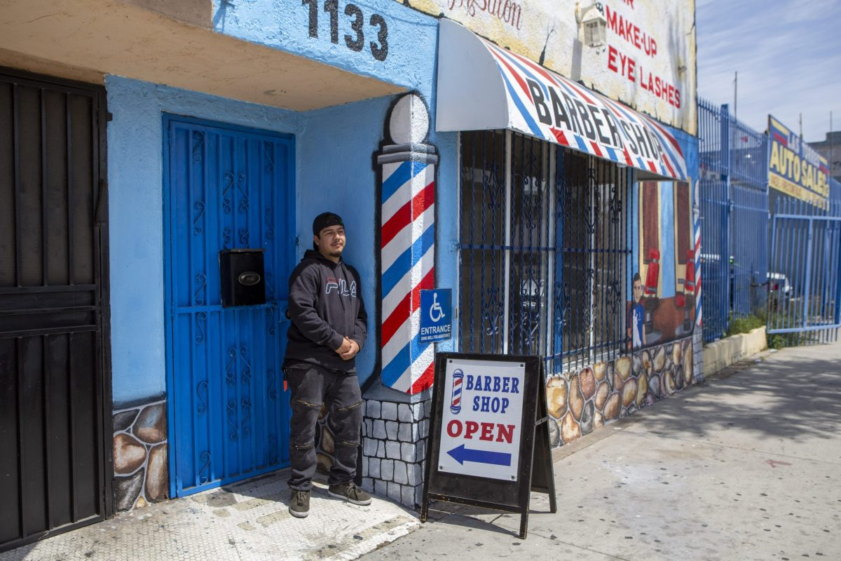 Daniel Sanchez stands in front of the doorway to his barbershop. The storefront's mural includes an old-fashioned red-and-blue barber's pole.