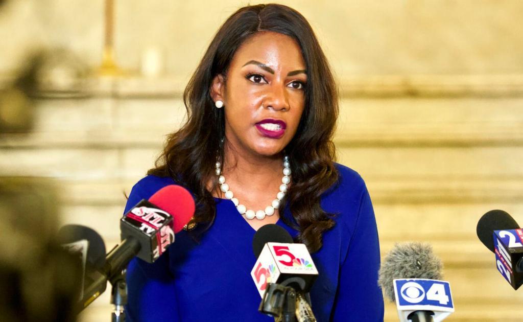 Tishaura Jones speaks into TV news station microphones.