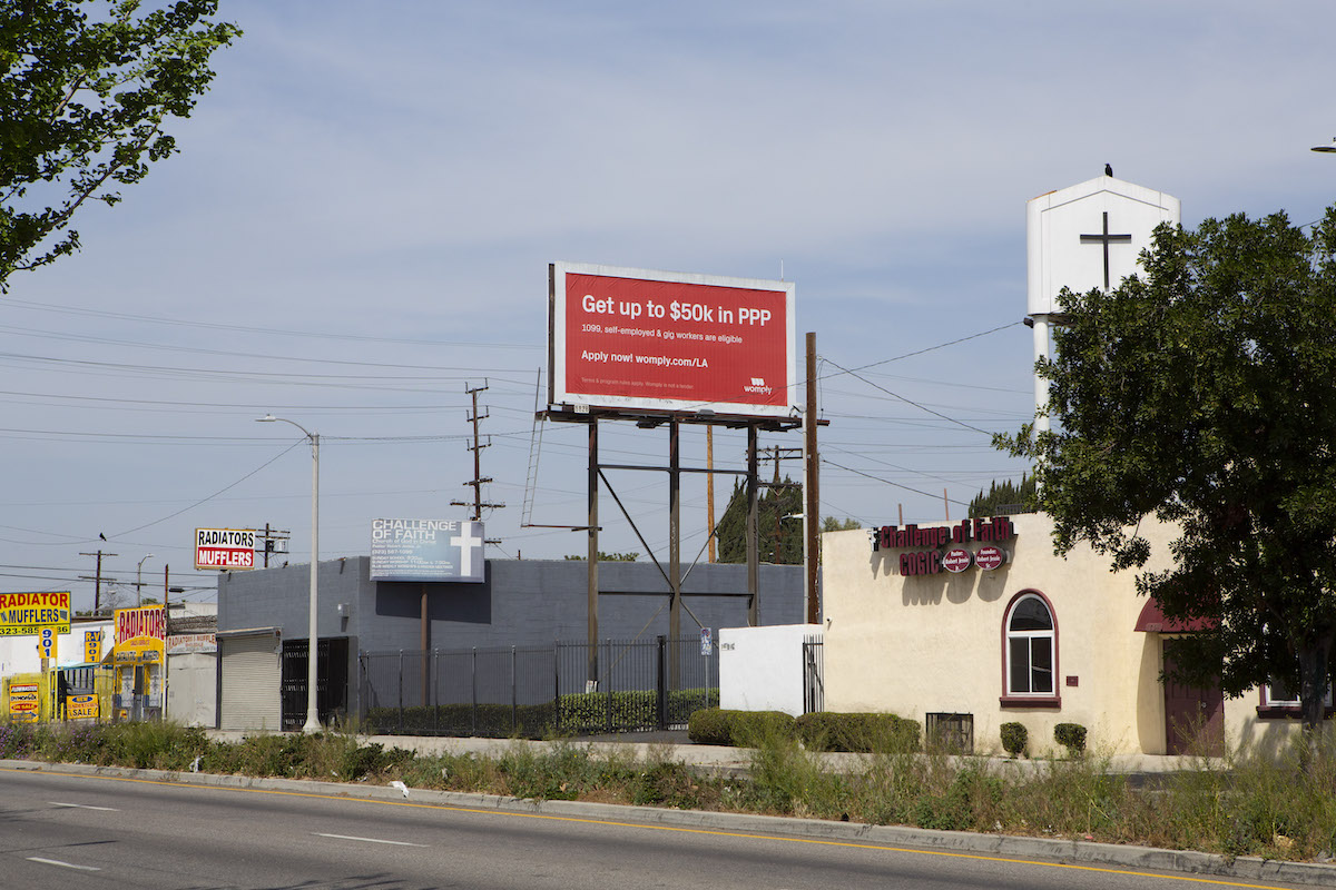 A billboard displays an advertisement for PPP loan assistance in South Central.