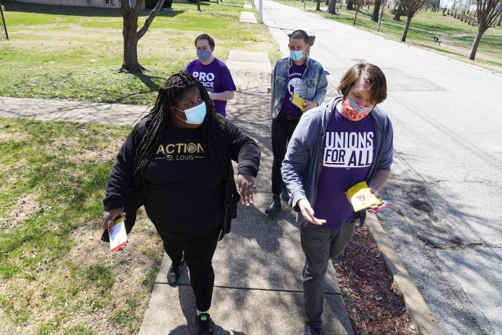 Kayla Reed and three volunteers walk down a sidewalk in a residential neighborhood.
