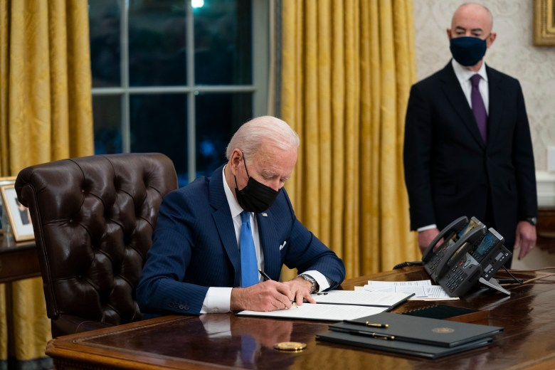 President Joe Biden, wearing a face mask, signs an executive order while seated at his desk in the White House Oval Office.