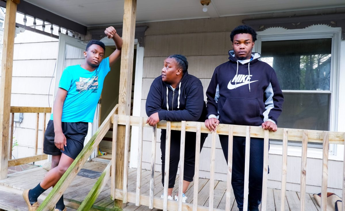 A Black family, two teenage sons and their mother, stands on the front porch of their home