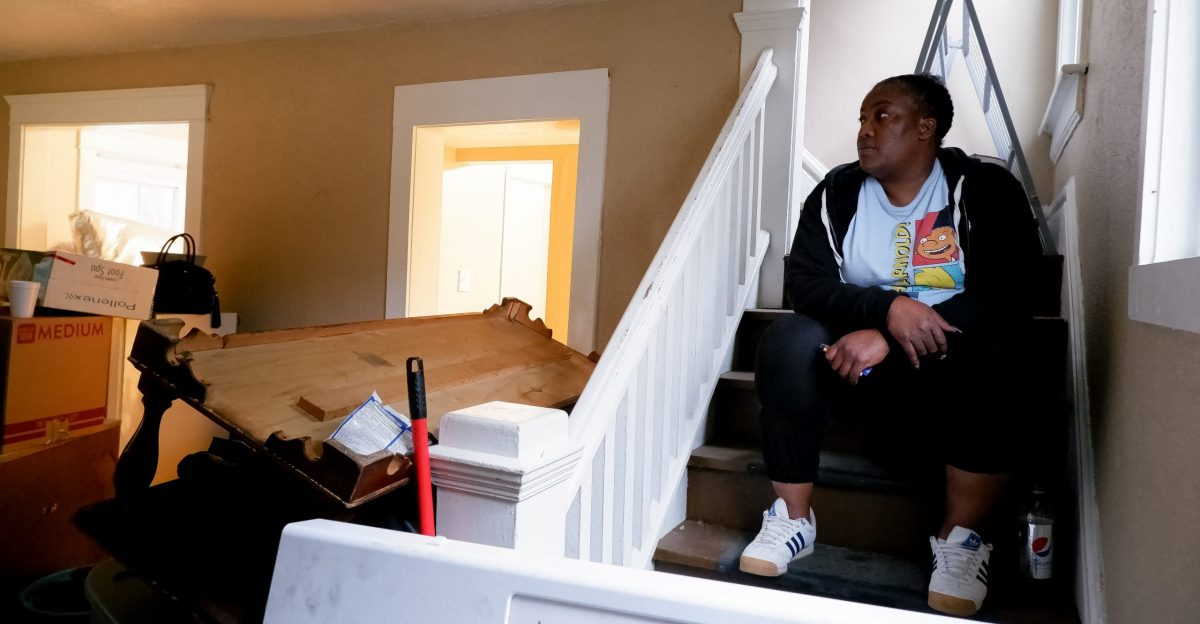 Amber Moreland sits on the stairs inside her rental home in Akron, Ohio, surrounded by boxes and furniture that she and her family are rushing to move.