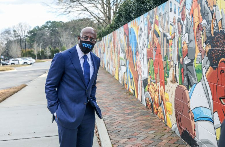 """Raphael Warnock stands near an outdoor mural. He wears a face mask that says, """"Vote."""""""