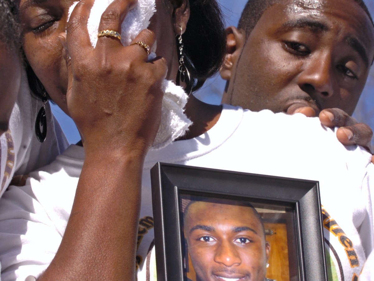 Billey Joe Johnson Sr., background, comforts his wife, Annette, who holds a photo of their son.