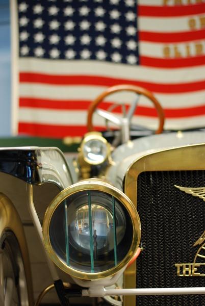 An American flag hangs behind a car.