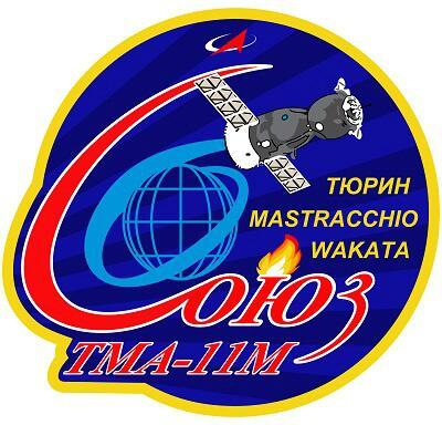 le logo de l'Expédition TMA-11 avec la flamme olympique