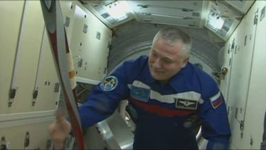 la torche olympique entre les mains du commandant de bord de l'ISS Fyodor Yurchikhin (image NASA TV)