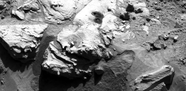 """Cette image de la caméra de navigation (NavCam) sur Curiosity montre deux trous dans la roche """"Windjana."""" Le trou le plus loin, avec un plus grand tas de résidus autour de lui, est un trou d'échantillonnage en pleine profondeur. Le trou le plus proche correspond au trou de test. Cette image a été prise le Sol 621 (5 mai) (source NASA / JPL-Caltech)"""