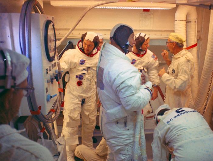 Dans la salle blanche au sommet du portique sur le Complexe de lancement 39 Pad A, les astronautes d'Apollo 11 sorte du vaisseau spatial Apollo après la répétition du lancement. Au premier plan, l'astronaute Buzz Aldrin. le responsable du pas de tir de Guenter Wendt parle avec Neil Armstrong. L'astronaute Michael Collins se place à gauche d'Armstrong (source NASA)