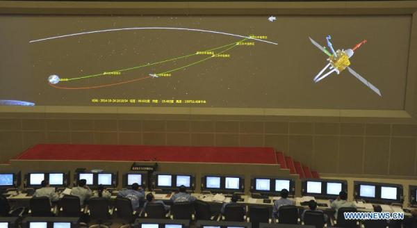 Photo du Beijing Aerospace Control Center qui montre sur l'écran la première correction de trajectoire pour la mission lunaire de test réalisée le 24 octobre 2014, sous le contrôle de techniciens (source Xinhua / Tian Zhaoyun)