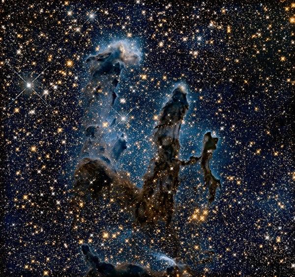 """Cette image montre les piliers en lumière infrarouge, ce qui lui permet de percer la poussière et les gaz . Dans cette vue éthérée, l'image entière est parsemée de brillantes étoiles et d'étoiles """"bébé"""" se formant dans les piliers eux-mêmes. Les contours fantomatiques des piliers semblent beaucoup plus délicats, et se détachent sur une étrange brume bleue. (Crédit: NASA , ESA / Hubble et l'équipe Hubble Heritage)"""