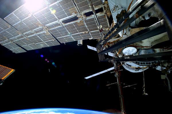 L'ATV5 attaché au module russe de l'ISS, la Terre et un panneau de la station. (Crédits : ESA)