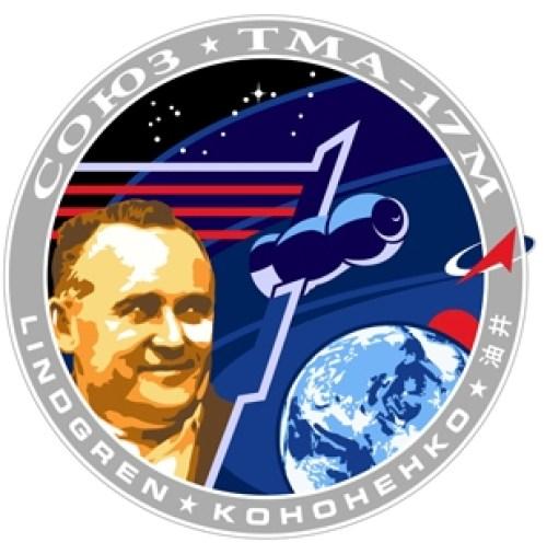"""Le patch Soyouz TMA-17M Il est inspiré du logo d'Apollo 17. Le principal élément de ce logo est un portrait de Sergueï Korolev, le légendaire """"principal constructeur"""", qui a façonné les premières années de l'astronautique soviétique. Derrière la Terre, un soleil rouge se lève, représentant l'élément japonnais de la mission. La constellation du Scorpion vient couronner le patch, avec l'étoile Antares, l'indicatif pour cette mission particulière Soyouz. Le timbre a été conçu par Luc van den Abeelen et Blake Dumesnil avec Oleg Kononenko. Droit d'auteur Roscosmos / spacepatches.nl"""