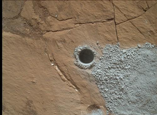 """Trou du perçage photographié par la caméra Malhi en bout de bras du rover Curiosity le 30 Juillet 2015, pendant le Sol 1060, sur une roche surnommée """"Buckskin"""" (Crédit image: NASA / JPL-Caltech / MSSS)"""