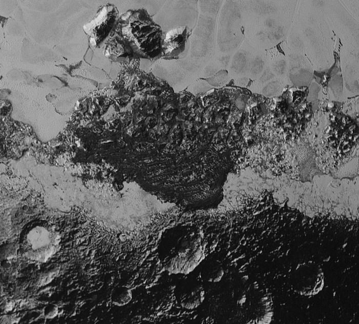 Un gros plan d'une zone sombre sur le bord de la zone de lumière en forme de coeur sur Pluton. (Credit: NASA/Johns Hopkins University Applied Physics Laboratory/Southwest Research Institute)