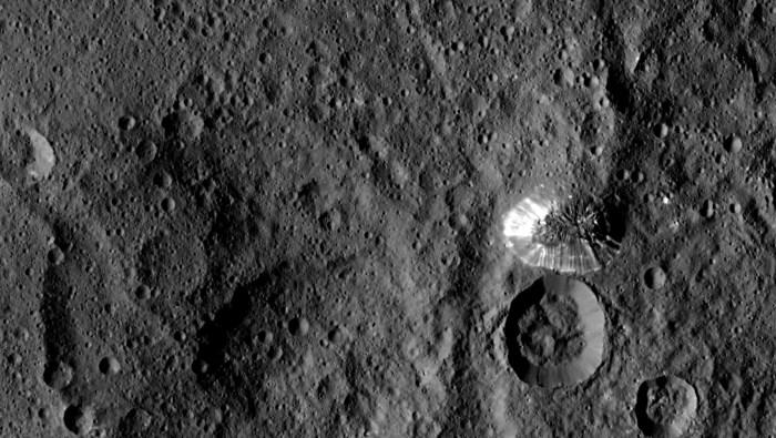 La sonde Dawn de la NASA a repéré cette montagne conique sur Ceres à une distance de 1470 kilomètres. Son périmètre est nettement défini, avec des débris presque pas accumulés à la base de la pente brillamment striée. L'image a été prise le 19 Août 2015. (Credit: NASA / JPL-Caltech / UCLA / MPS / DLR / IDA)