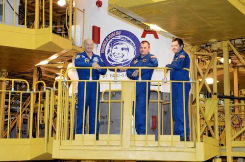 Les astro/cosmonautes Jeff Williams, Alexey Ovchinin et Oleg Skripochka posant devant la coiffe du lanceur Soyuz TMA-20M arborant le logo de l'année Gagarine (Credit: RSC Energia)