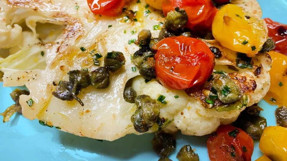 A cauliflower steak topped with brown butter, capers, and tomatoes.
